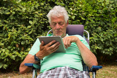 Hombre mayor con la tableta digital Imagenes de archivo