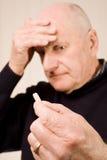 Hombre mayor con la tablilla o la píldora de la explotación agrícola del dolor de cabeza Imágenes de archivo libres de regalías