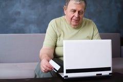 Hombre mayor con la tarjeta de crédito que hace el pago en línea fotos de archivo libres de regalías