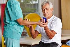 Hombre mayor con las bolas del spikey en gimnasio Imágenes de archivo libres de regalías