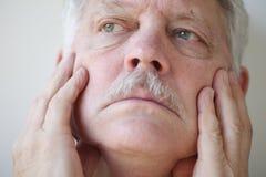 Hombre mayor con las manos en cara Imagen de archivo libre de regalías