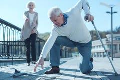 Hombre mayor con las muletas que golpean la tierra Fotos de archivo libres de regalías