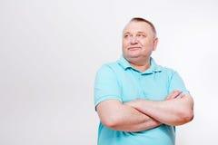 Hombre mayor con los brazos cruzados sobre blanco Foto de archivo