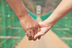 Hombre mayor con los pares de la mujer que llevan a cabo las manos que camina en el bridg Fotografía de archivo libre de regalías