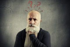 Hombre mayor con los signos de interrogación rojos sobre la cabeza imágenes de archivo libres de regalías
