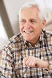 Hombre mayor con los vidrios que se relajan en silla Fotografía de archivo libre de regalías