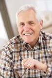 Hombre mayor con los vidrios que se relajan en silla en el país Imágenes de archivo libres de regalías