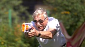 Hombre mayor con lucha del arma del juguete en la naturaleza imagen de archivo libre de regalías
