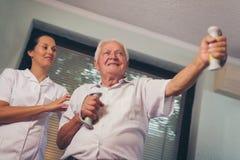 Hombre mayor con pesas de gimnasia en la rehabilitación Fotografía de archivo libre de regalías