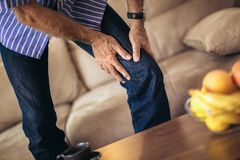 Hombre mayor con problemas crónicos de la rodilla fotos de archivo libres de regalías