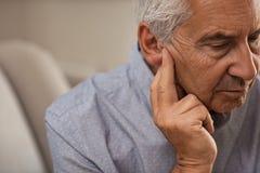 Hombre mayor con problemas de la audiencia imagen de archivo