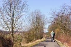 hombre mayor con rollator en un día de invierno bikeway y soleado Foto de archivo