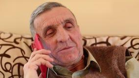Hombre mayor con smartphone rojo almacen de video