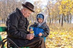 Hombre mayor con su nieto en el parque Imágenes de archivo libres de regalías