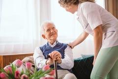 Hombre mayor con un bast?n que es confortado por la enfermera en el hospicio imagenes de archivo