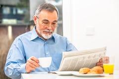 Hombre mayor con un periódico Fotos de archivo
