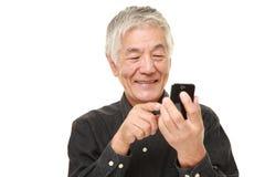 Hombre mayor con un teléfono elegante Fotos de archivo libres de regalías