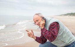 Hombre mayor con un teléfono en fondo del mar Imagen de archivo libre de regalías