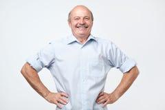 Hombre mayor con una mirada orgullosa, satisfecha y feliz, con ambas manos en caderas imagenes de archivo