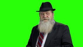 Hombre mayor confiado con la barba en la pantalla verde almacen de metraje de vídeo