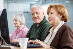 Hombre mayor confiado con los amigos femeninos en clase del ordenador Fotografía de archivo libre de regalías