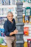 Hombre mayor confiado que apila las cajas de herramientas en tienda Fotos de archivo libres de regalías