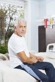 Hombre mayor confiado que se sienta en cama en el centro de rehabilitación Imágenes de archivo libres de regalías