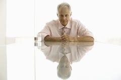 Hombre mayor confiado que se sienta en la mesa de reuniones Imagen de archivo libre de regalías