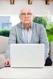 Hombre mayor confiado que usa el ordenador portátil en la clínica de reposo Imagenes de archivo