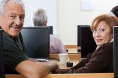 Hombre mayor confiado y mujer que se sientan en clase del ordenador Fotografía de archivo