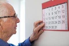 Hombre mayor confuso con la demencia que mira el calendario de pared foto de archivo