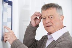 Hombre mayor confuso con la demencia que mira el calendario de pared fotografía de archivo libre de regalías