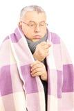 Hombre mayor cubierto con la manta y la corbatería que tosen debido a Fotografía de archivo libre de regalías