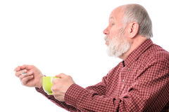 Hombre mayor de Cheerfull con la taza verde y la cucharilla, aisladas en blanco Foto de archivo