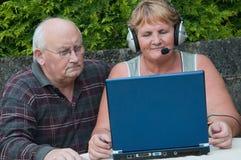 Hombre mayor de la mujer en la computadora portátil afuera Imagenes de archivo