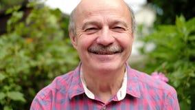 Hombre mayor mayor de la sonrisa feliz en el parque al aire libre almacen de video