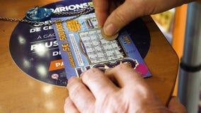Hombre mayor de la vista lateral que rasguña el boleto de lotería que gana efectivo premiado almacen de metraje de vídeo