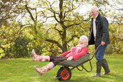 Hombre mayor de los pares que da paseo de la mujer en carretilla Imagenes de archivo