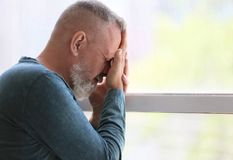 Hombre mayor deprimido cerca de la ventana dentro Foto de archivo