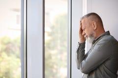 Hombre mayor deprimido cerca de la ventana dentro Fotos de archivo