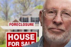 Hombre mayor deprimido delante de la muestra y de la casa de la ejecución de una hipoteca Fotografía de archivo libre de regalías