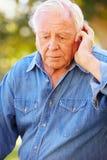Hombre mayor deprimido que se sienta afuera Foto de archivo libre de regalías