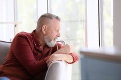Hombre mayor deprimido que se sienta en butaca dentro Foto de archivo libre de regalías