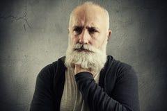 Hombre mayor desanimado sobre backround gris foto de archivo