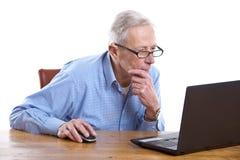 Hombre mayor detrás del ordenador fotos de archivo