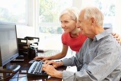Hombre mayor e hija que usa el ordenador en casa imagenes de archivo