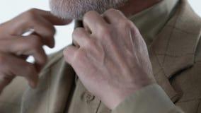Hombre mayor elegante que pone en la chaqueta y que abotona la camisa, estilo de la ropa de la moda metrajes
