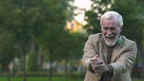 Hombre mayor emocionado debajo de la lluvia del dinero, triunfo de la lotería, éxito de la inversión, fortuna almacen de video