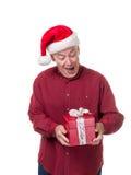 Hombre mayor emocionado que consigue un regalo de la Navidad Imagenes de archivo