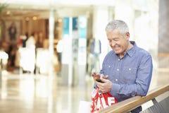 Hombre mayor en alameda de compras usando el teléfono móvil Imagenes de archivo